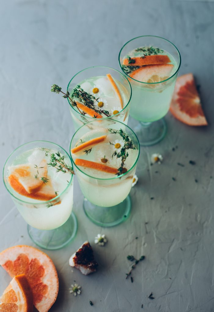 Four grapefruit & thyme spritzers showing the herbal thyme garnishes and grapefruit wedges.
