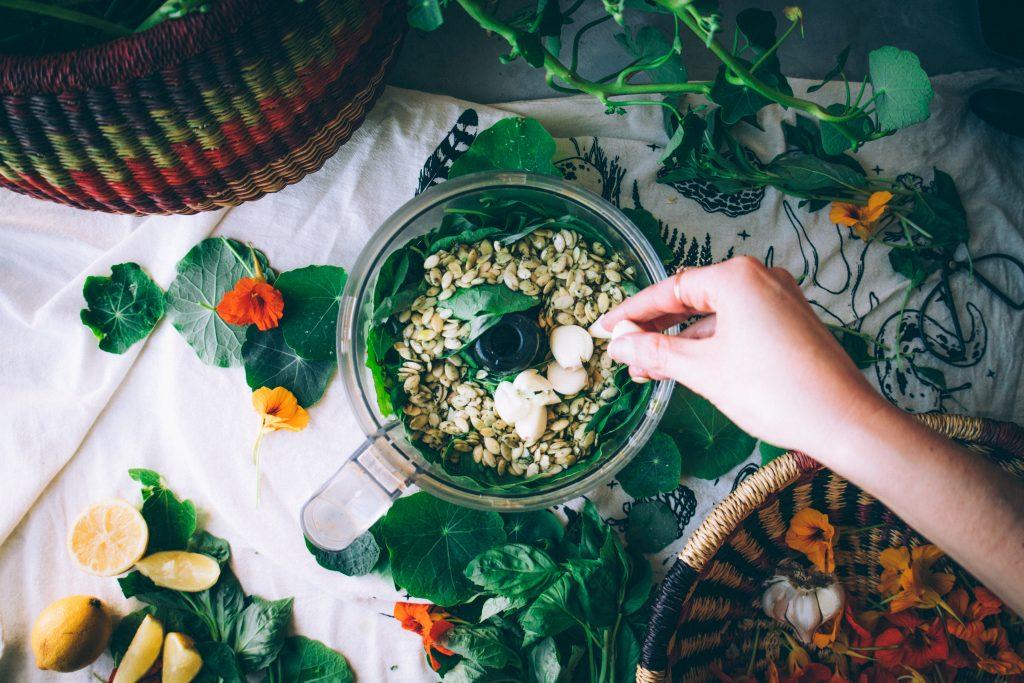 Adding garlic to the food processor for pesto