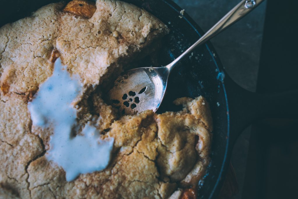 A scoop of peach cobbler and some ice cream on top.