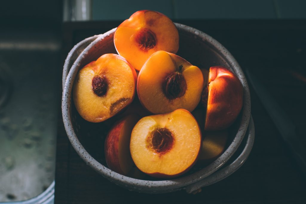 Fresh peaches, cut open showing their beautiful yellow color.