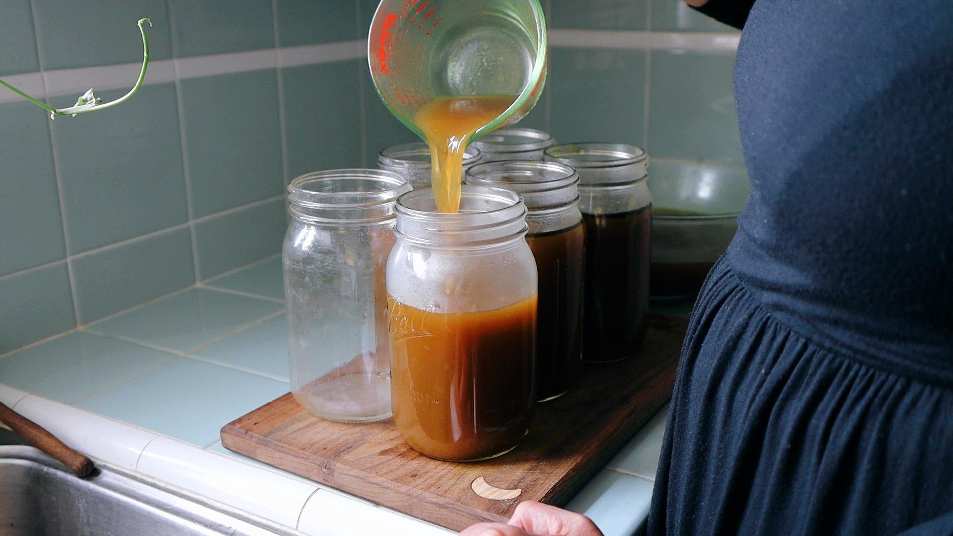 Pouring bone broth into jar